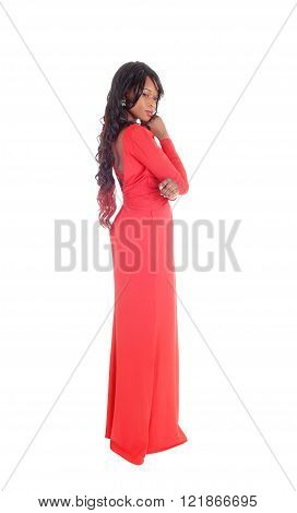 A lovely slim African American woman in a long red dress and curly long black hair standing in profile isolated for white background. ** Note: Visible grain at 100%, best at smaller sizes