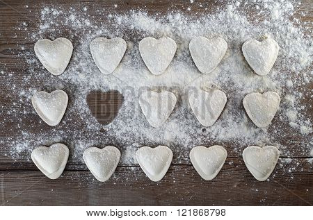 Heart shaped ravioli sprinkle with flour on wooden background. Uncooked ravioli hearts. Cooking dumplings. Top view.