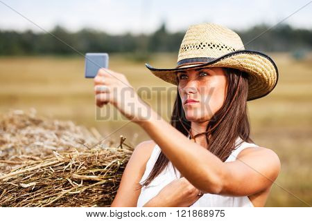 Woman in cowboy hat looking at the mirror.