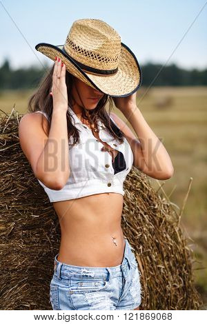 Girl holding cowboy hat.