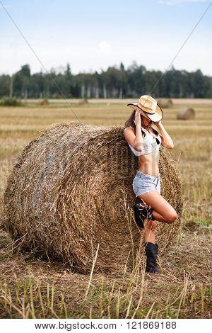 Woman in cowboy hat near a straw bale