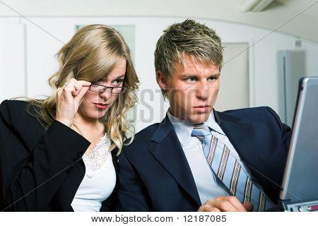 Schlechte Nachrichten für zwei Geschäftsleute, die an einem Laptopcomputer arbeiten