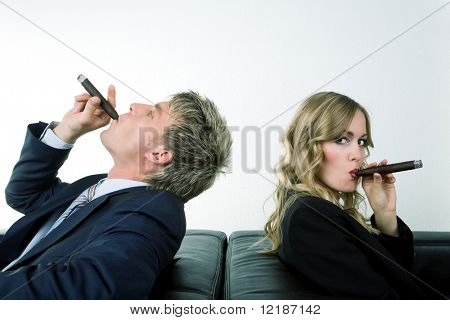 Two business people (male / female) smoking cigars looking in different directions