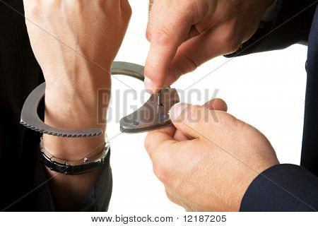 man unlocking handcuffs that bind him to a woman (close-up)