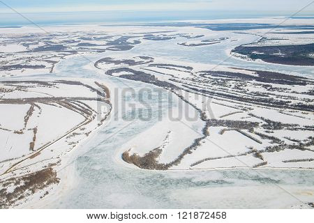 Aerial view of the great river with floating ice floes during sundown. Drifting of ice. Driving of i