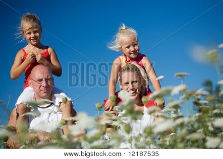 A young family with two cute daughters sitting on the shoulders of the parents, all in a field of yarrow