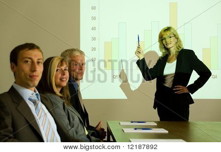 A group of people in a video presentation held by a blond woman, whole group looking at the viewer