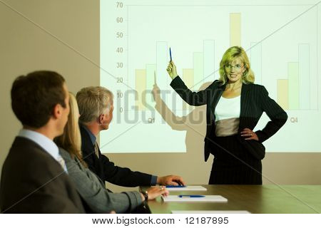 A group of people in a video presentation held by a blond woman
