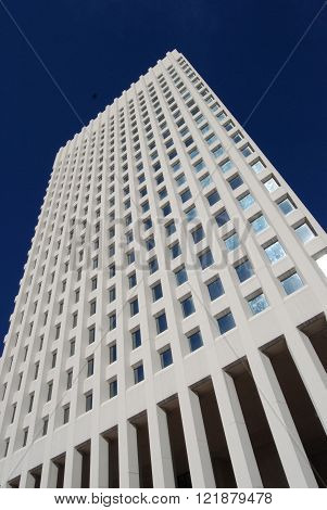 White stone building with grid layout windows on a blue sky.