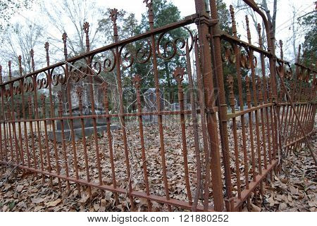 An old, rusty cemetery fence and gate, containing a single family plot.