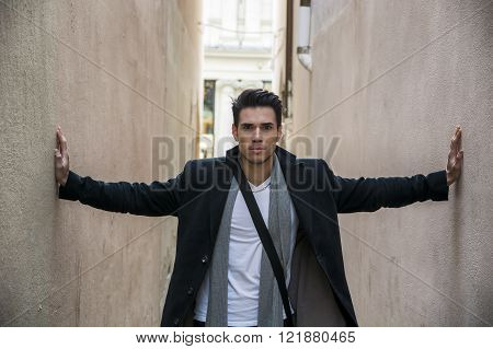 Young man pressed between two walls. Oppression, anxiety