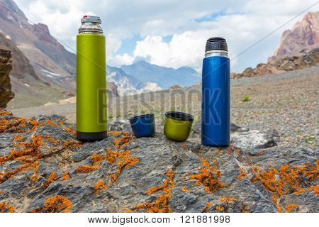 Two travel thermoses on stone