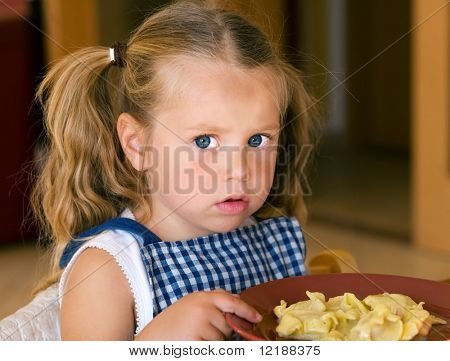 Young girl and a plate of pasta, she looks rather skeptical