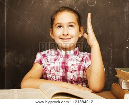 cute little real girl pupil in classroom at blackboard writting, girl school, ready to answer close up, education concept
