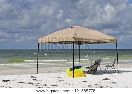 Portable Shelter with Chairs and Floatation Devices on the Beach