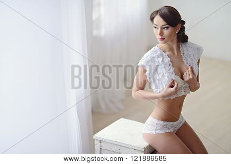 Beautiful sexy lady in elegant white panties and bra. Fashion portrait of model indoors. Beauty brunette woman with attractive body in lace lingerie. Female ass in underwear. Naked girl
