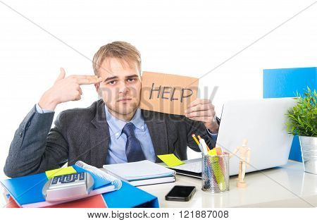 young desperate businessman holding help sign looking worried suffering work stress sitting at computer desk on white background office in business project problem
