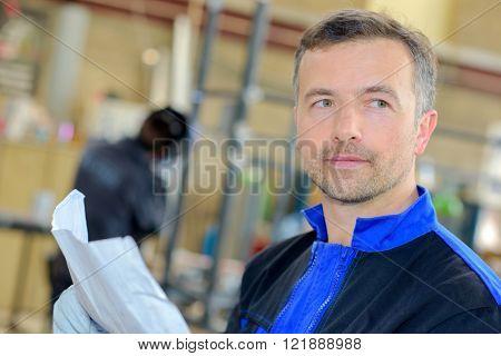Closeup of workman holding paperwork