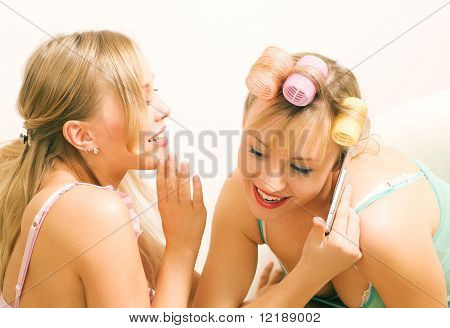Two women with curlers doing beauty things, using a cell phone, and telling each other secrets