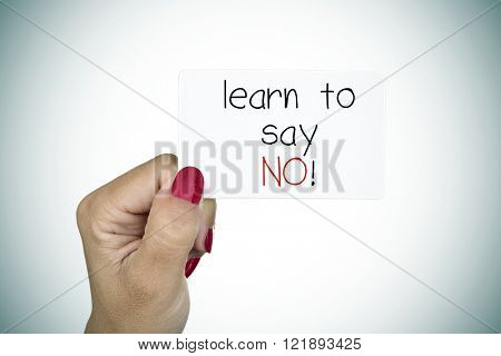 closeup of the hand of a young woman with red polished nails holding a signboard with the text learn to say no