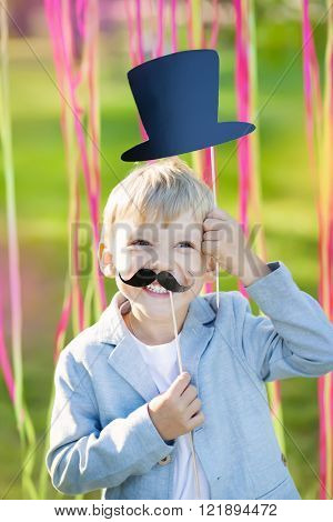little boy with funny paper mustache and hat. Cheerful children's holiday outdoors.