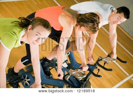 Three People Cycling In A Gym Or Fitness Club, Dressed In Colorful Clothes; Focus On The Girl In Green