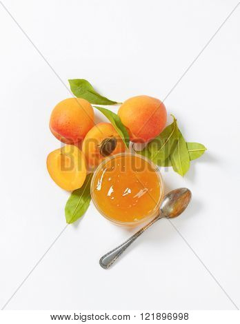 fresh apricots and bowl of apricot jam on white background