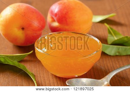 fresh apricots and bowl of apricot jam on wooden table - close up