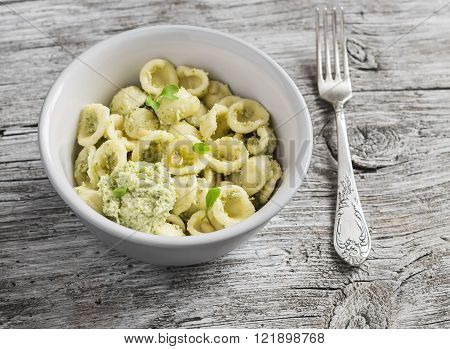 Delicious healthy vegetarian pasta with broccoli and pine nuts pesto in ceramic bowl on light rustic wooden board