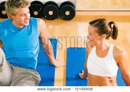 Couple in the gym flirting in a break between two training sessions