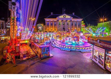 GRONINGEN THE NETHERLANDS-MAY 52015: Annual Funfair during may holidays on the Grote Markt cenral city square. Long exposure image at night with blurred movement.