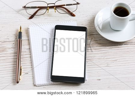 Notebook with glasses pencil smart phone and coffee cup on wooden table