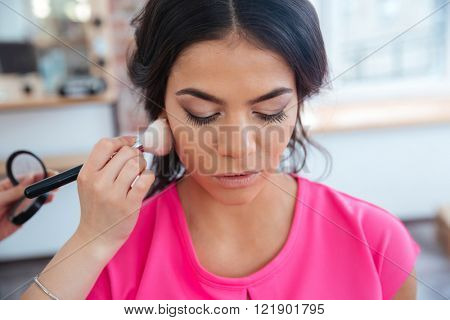 Makeup artist doing makeup to thoughtful pretty young woman in pink top with dark hair