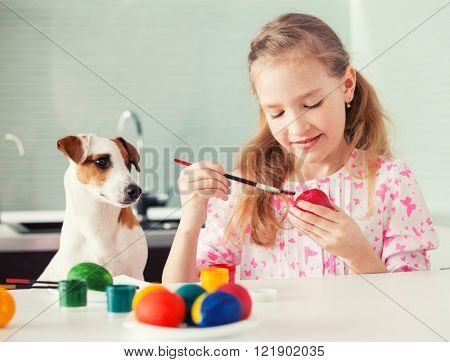Easter. Child with dog painting eggs