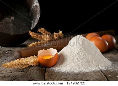 handful of flour with egg rolling pin sieve and spikelets of wheat on a black background closeup with copy space