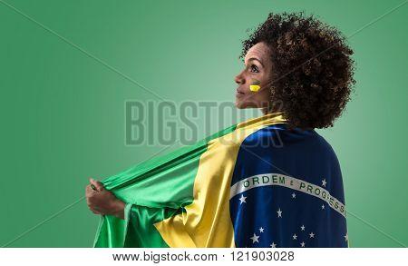 Brazilian woman holding the Brazilian flag on green background
