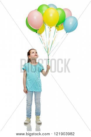 childhood, fashion, imagination and people concept - happy little girl looking up and holding bunch of colorful helium balloons on strand