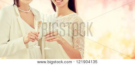 people, homosexuality, same-sex marriage, celebration and love concept - close up of happy married lesbian couple holding and clinking champagne glasses over pink holidays lights background