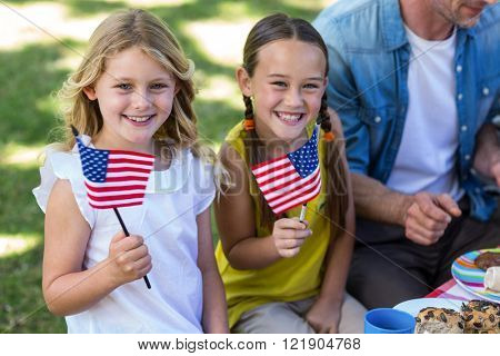 Family with American flag having a picnic in a park