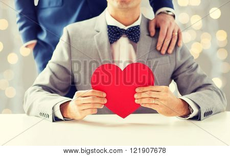 people, homosexuality, same-sex marriage, valentines day and love concept - close up of happy married male gay couple with red paper heart shape on wedding over holidays lights background