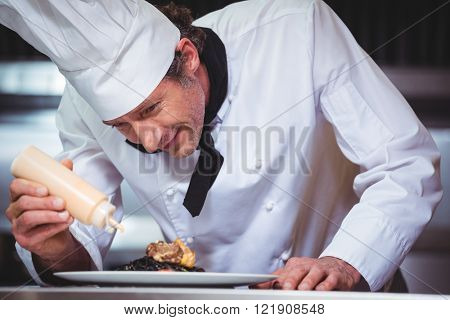 Chef putting sauce on a dish of spaghetti in commercial kitchen