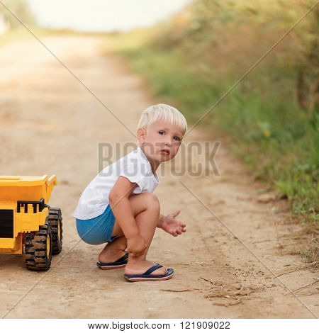 Adorable little blond boy playing with big yellow car outdoors.