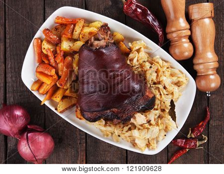 Roasted pork knuckle with baked potato, carrot and sour cabbage