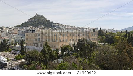 ATHENS GREECE - MAY 02: Greek Parliament in Athens on MAY 02 2015. Bunch of Tourists in front of Hellenic Parliament Building and Mount Lycabettus in Athens Greece.