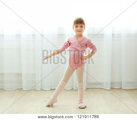 Little cute girl in pink leotard making new ballet movement at dance studio