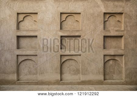 Many small arches on the grunge wall. Interior details of old arabic house.