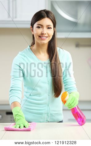 Beautiful woman in protective gloves cleaning kitchen table with rag and spray