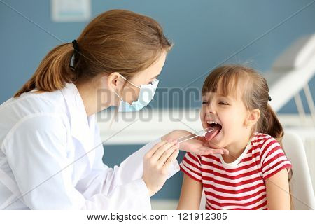 Doctor checking little girl's throat in the office