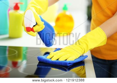 Woman in protective gloves cleaning electrical hob with rag and spray