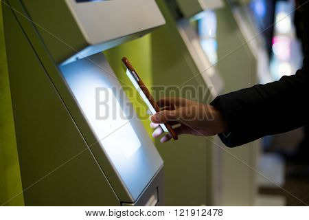 Woman scanning on the payment machine by NFC